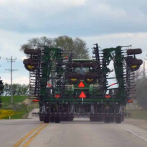 A color photo of a farm tractor towing a piece of tillage equipment