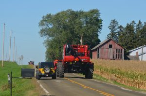A yellow Jeep passing a red tractor on a rural road