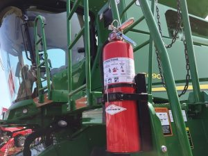 Color photo of a 10 lb ABC fire extinguisher on a grain combine