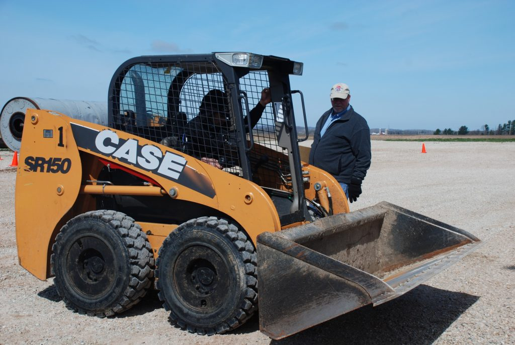 Operator of a Case skid steer receiving safety training from an instructor.