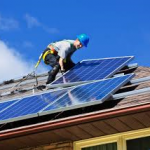 Man on residence rooftop installing solar panels