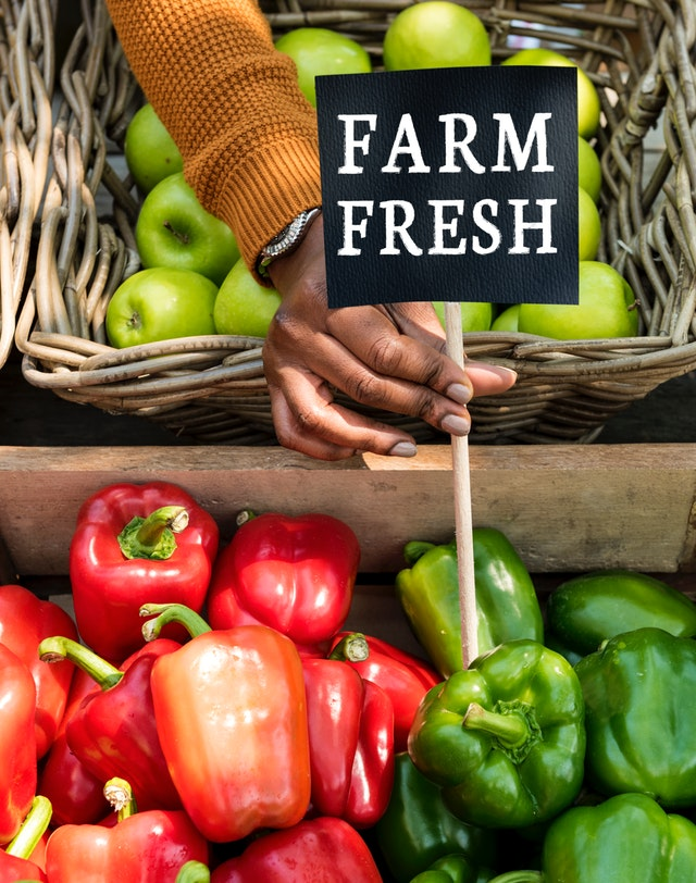 person holding sign farm fresh over bell peppers