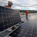 worker's installing solar panels on industrial roof