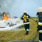 firefighters extinguishing car fire with foam