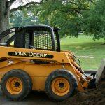 yellow orange John Deere skid steer loading soil