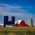 picture of farm with blue silos and windmills