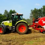 picture of a light green tractor & red baler