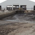 picture of a manure pit near a white barn