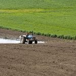 farm worker plwing the field on a blue tractor