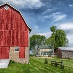 picture of a red barn with a house & shed in the background