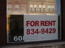 For rent sign in a storefront window.