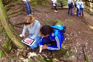 Adults using digital microscope outdoors