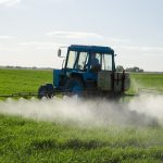 blue tractor spraying pesticides in the field