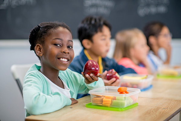 girl at school eating an apple