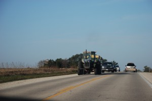 Image of agricultural equipment and motor vehicles on a divided two lane highway.