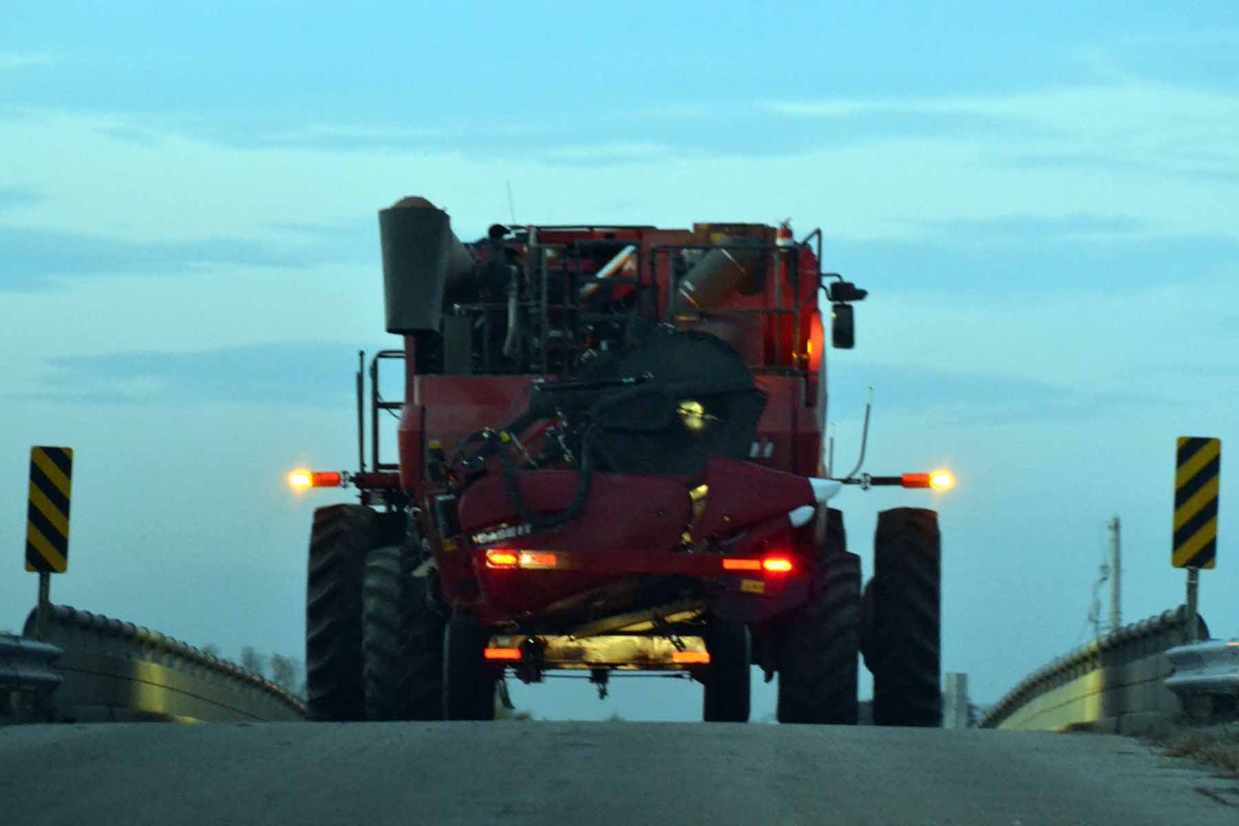 A color photo of a John Deere combine operted crossing a bridge during hours of darkness.