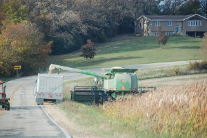 Color photo of a combine loading a semi-trailer parked on a road right of way.