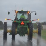 color photo of a John Deere farm tractor operating on a Wiscosnin highway during a hours of darkenss due to rain.