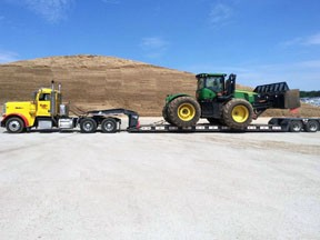 Color photo of a John Deere packing tractor being trailered by a truck tractor and low-boy trailer.