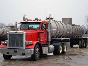 A color photo of a truck tractor and tanker used for apply manure.