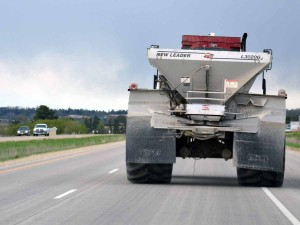 Color photo of a truck mounted fertilizer spreader operating on a highway.
