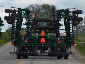A color photo of a John Deere tractor towing a field cultivator. This is an example of an IoH Category B combination meeting lighting and marking requirements for a wide IoH as it operates on a state highway.