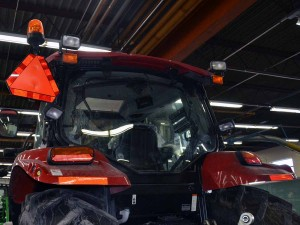 A color photo of the rear view of a farm tractor with lamps and markings for an IoH.