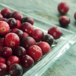 Ripe red cranberries on a square plate on a slate blue-gray background.