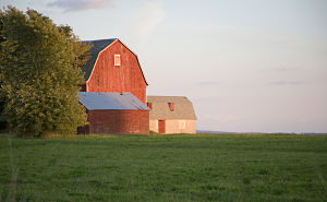 Image of red barn and hay field.