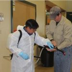Photo of a man in a white coverall suit wearing a backpack sprayer with another man standing nearby helping adjust sprayer settings. Demonstration of safety while using a backpack sprayer.
