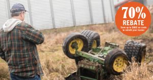 farmer in plaid jacket and baseball cap looking at rolled over tractor in front of grain bin
