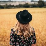 woman with black hat in front of small grain field ready for harvest