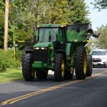 Green tractor and wagon on paved road with double solid line being followed by a white SUV.