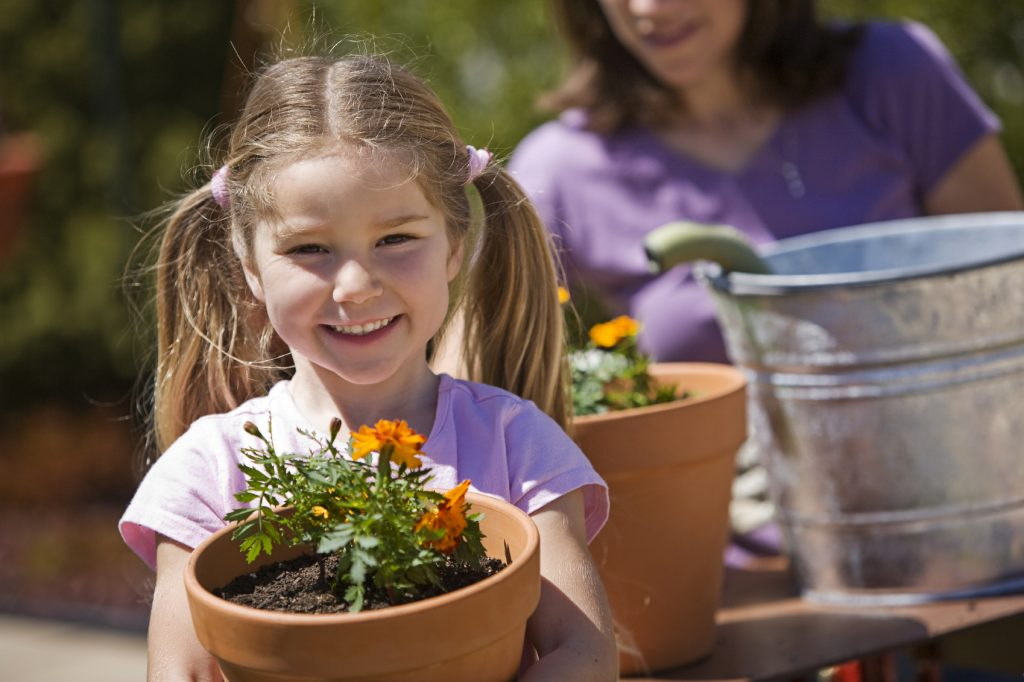 young girl with marigold in terracotta pot, adult with marigold in terracotta pot in background.