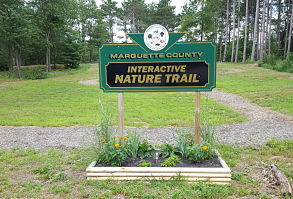 Picture of the Marquette County Interactive Nature Trail sign that can be viewed from Highway C. Sign is green and black with gold lettering and features the Marquette County seal. The Master Gardener Prairie Area can be seen behind the sign.