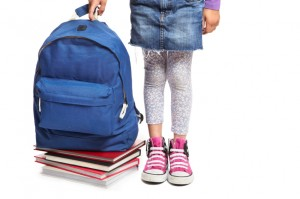 School girl with books and backpack