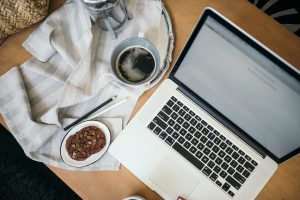 laptop computer on table with coffee cup and plate of cookies