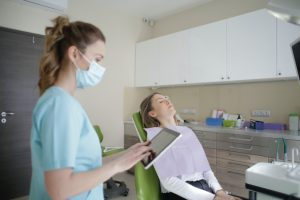 Dental assistant with patient