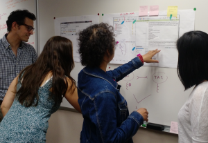 Four people stand at a white board looking at diagrams.
