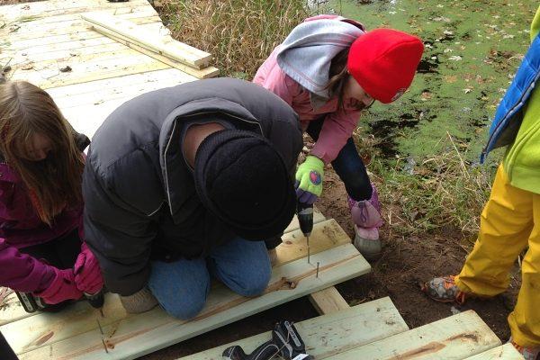 Girls building wooden boardwalk