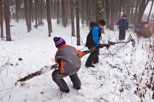 Children collecting logs for outdoor survival program